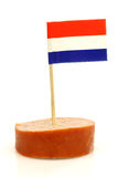 A piece of smoked sausage. With Dutch flag toothpicks on a white background Royalty Free Stock Photos