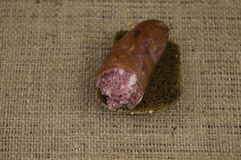 A piece of smoked sausage with bread royalty free stock images