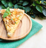 Piece of snack puff pastry pie or quiche with camembert cheese, pear, walnuts and fresh mint Stock Photo