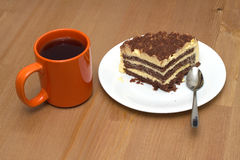 A piece of sponge cake on a plate and cup of tea close-up Royalty Free Stock Photos