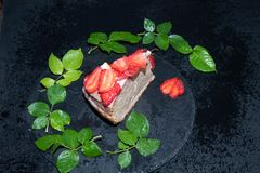 A piece of sponge cake with sour cream cream, fresh strawberries on top, lay on a black tray, stock photography