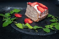 A piece of sponge cake with sour cream cream, fresh strawberries on top stock image