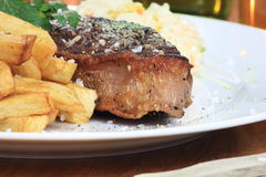 Piece of steak with chips on a plate. Stock Photos