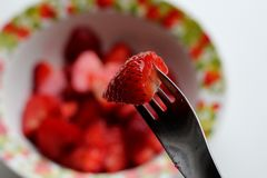 A piece of strawberries on a fork on a background of strawberries in a bowl. White background. Top view. stock images