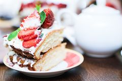 A piece of strawberry cake in cream and mint leaves on a table in a plate stock photography
