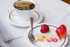 Piece of strawberry dessert on white plate and Cup coffee. A piece of strawberry dessert on a white plate with a Cup of coffee Stock Photo