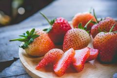 Piece of strawberry fruit , on wood table , fruit for health.  Stock Photos
