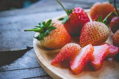 Piece of strawberry fruit , on wood table , fruit for health.  Royalty Free Stock Photography