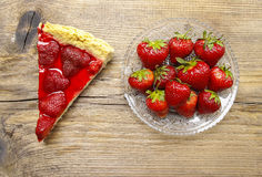 Piece of strawberry tart and fresh raw strawberries. On wooden table Royalty Free Stock Image