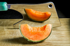 Piece of succulent melon rests on the Board with an axe Stock Photo