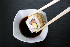 Piece of sushi dipping in soy sauce Stock Photography
