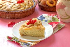 Piece of sweet peach cake with red currants Royalty Free Stock Image