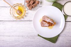 A piece of sweet round fruit homemade cake, on a white dish on a wooden table, served with a cup of milk.  royalty free stock images