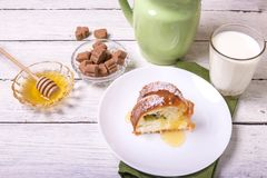 A piece of sweet round fruit homemade cake, on a white dish on a wooden table, served with a cup of milk.  stock images