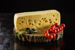 Piece of Swiss cheese, cherry tomatoes and olives on wooden boar. D over black Stock Photo