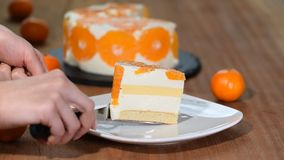 A piece of tangerine cake isolated in white plate on the wooden table.  stock footage