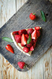 Piece of tart with custard and strawberries Royalty Free Stock Images