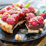 Piece of tartlets with chocolate and raspberry close up. Piece of tartlets with chocolate and raspberry on a fork close up, selective focus Stock Photos