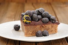 Piece of tasty chocolate pie with ganache, decorated with fresh Stock Image