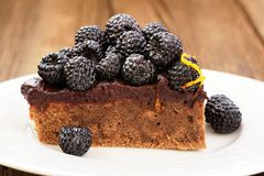 Piece of tasty chocolate pie with ganache, decorated with fresh Royalty Free Stock Photo