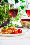 Piece of tasty hot lasagna with red wine Royalty Free Stock Photography