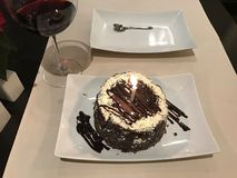 Anniversary chocolate cake and some red wine. A piece of a testy chocolate cate in a plate and a glass with red wine near Stock Photos