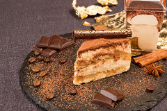 Piece of tiramisu cake on black slate garnish with mint and choc Royalty Free Stock Photography