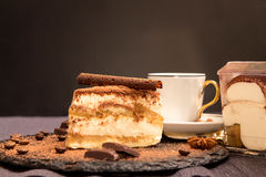 Piece of tiramisu cake on black slate garnish with mint and choc Stock Image