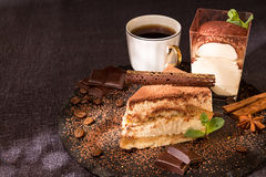 Piece of tiramisu cake on black slate garnish with mint and choc Royalty Free Stock Photo