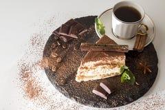 Piece of tiramisu cake on black slate stock photos