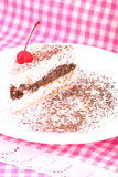 Piece of tiramisu on checkered table-cloth Stock Image