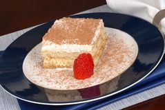 A piece of tiramisu dusted with cocoa on a blue plate Stock Photo
