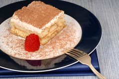 A piece of tiramisu dusted with cocoa with a fork on a blue plat Royalty Free Stock Photography