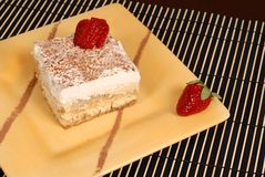 A piece of tiramisu dusted with cocoa on a yellow plate with two Stock Image
