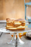 Piece of toffee and vanilla cake on transparent glass cake stand Royalty Free Stock Photos