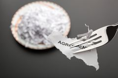 Piece of torn agreement on the fork Stock Images