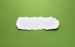 A piece of torn paper on a green background Royalty Free Stock Photo