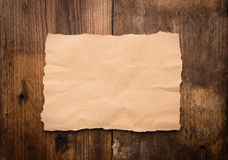 Piece of torn paper on old grunge wood Royalty Free Stock Photo