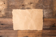 Piece of torn paper on old grunge wood. En table royalty free stock image