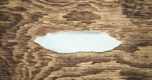 Piece of torn paper on wood background royalty free stock photo