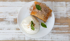 Piece of traditional apple strudel pie served with ice-cream, fresh mint, raspberry and glass of wine Royalty Free Stock Photography
