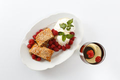 Piece of traditional apple strudel pie served with ice-cream, fresh mint, raspberry and glass of wine Stock Photography