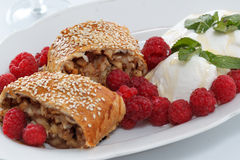 Piece of traditional apple strudel pie served with ice-cream, fresh mint, raspberry and glass of wine Royalty Free Stock Photo