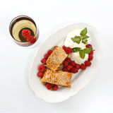 Piece of traditional apple strudel pie served with ice-cream, fresh mint, raspberry and glass of wine Stock Image