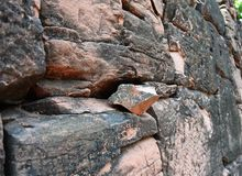 Piece of triangle ancient rock on the wall Royalty Free Stock Photos