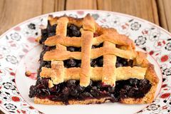 Piece of triangular homemade lattice pie with whole wild blueberries  Stock Photo