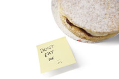 Piece of Victoria sponge cake with 'don't eat me' sign on sticky notepaper Stock Photo