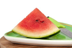 A piece of watermelon and knife on green plate Royalty Free Stock Image