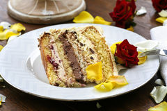 Piece of wedding cake among rose petals Stock Photography