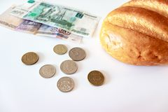 A piece of white bread, coins and paper rubles on the table. The concept of poverty, lack of money for food.  royalty free stock photos